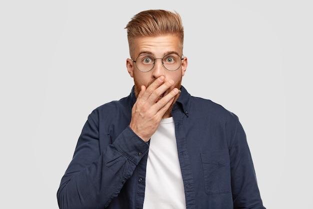 Jonge foxy man met verbijsterde uitdrukking bedekt mond met handpalm, heeft bezorgde uitdrukking, trendy kapsel, kan niet geloven in slecht nieuws, staat tegen een witte muur. mensen, emoties concept
