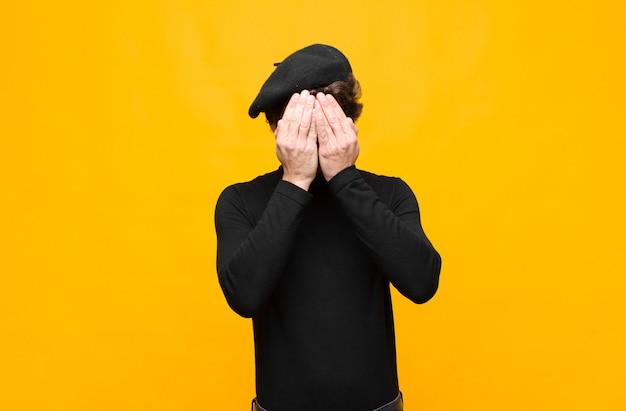 Jonge franse kunstenaar man verdrietig, gefrustreerd, nerveus en depressief, gezicht met beide handen, schreeuwend tegen oranje muur
