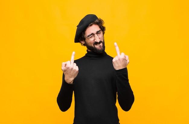 Jonge franse kunstenaar man voelt provocerend, agressief en obsceen, flipping de middelvinger, met een opstandige houding tegen oranje muur