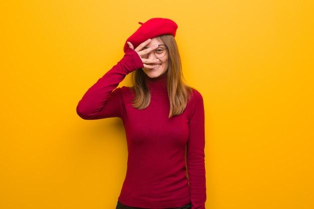 Jonge franse kunstenaarsvrouw die in verlegenheid wordt gebracht en tegelijkertijd lacht
