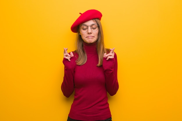 Jonge franse kunstenaarsvrouw die vingers kruisen voor het hebben van geluk