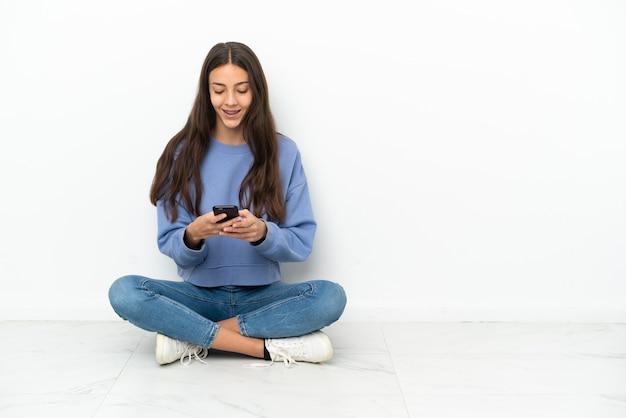 Jonge franse meisjeszitting op de vloer die een bericht met mobiel verzendt