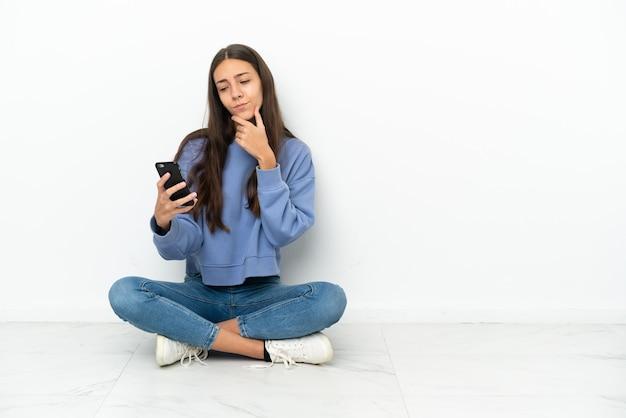 Jonge franse meisjeszitting op de vloer die en een bericht denkt verzenden