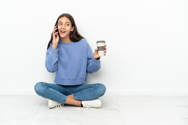 Jonge franse meisjeszitting op de vloer die koffie houdt om mee te nemen en een mobiel
