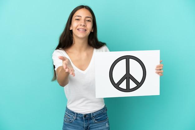 Jonge franse vrouw die op blauwe achtergrond wordt geïsoleerd die een aanplakbiljet met vredessymbool houdt dat een overeenkomst sluit
