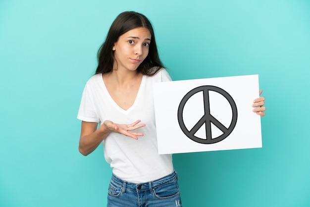 Jonge franse vrouw die op blauwe achtergrond wordt geïsoleerd die een aanplakbiljet met vredessymbool houdt en het richt