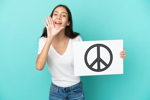 Jonge franse vrouw die op blauwe achtergrond wordt geïsoleerd die een aanplakbiljet met vredessymbool houdt en schreeuwt