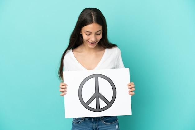 Jonge franse vrouw die op blauwe achtergrond wordt geïsoleerd die een aanplakbiljet met vredessymbool houdt