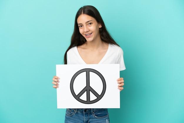 Jonge franse vrouw die op blauwe achtergrond wordt geïsoleerd die een aanplakbiljet met vredessymbool met gelukkige uitdrukking houdt