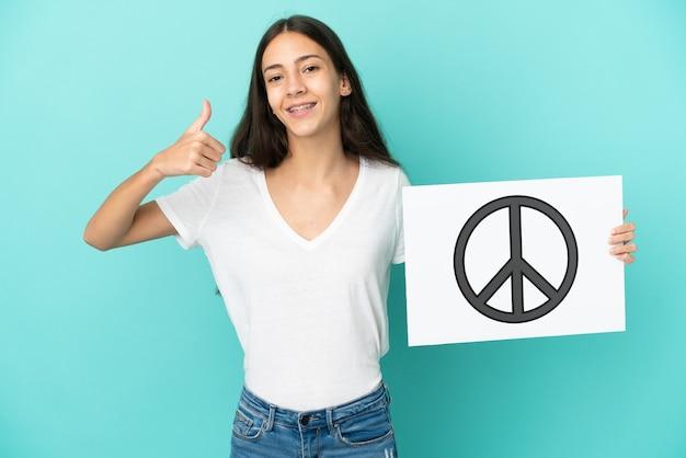 Jonge franse vrouw die op blauwe achtergrond wordt geïsoleerd die een aanplakbiljet met vredessymbool met omhoog duim houdt