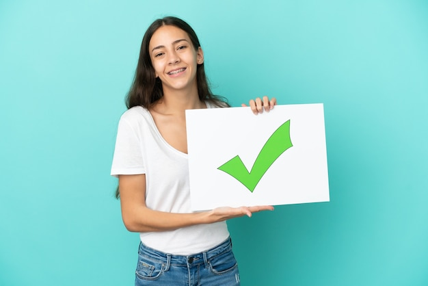 Jonge franse vrouw geïsoleerd met een bordje met tekst groen vinkje met vrolijke uitdrukking
