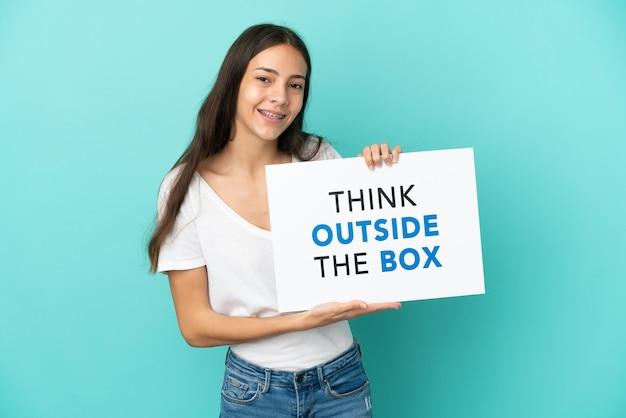 Jonge franse vrouw geïsoleerd met een bordje met tekst think outside the box met gelukkige uitdrukking