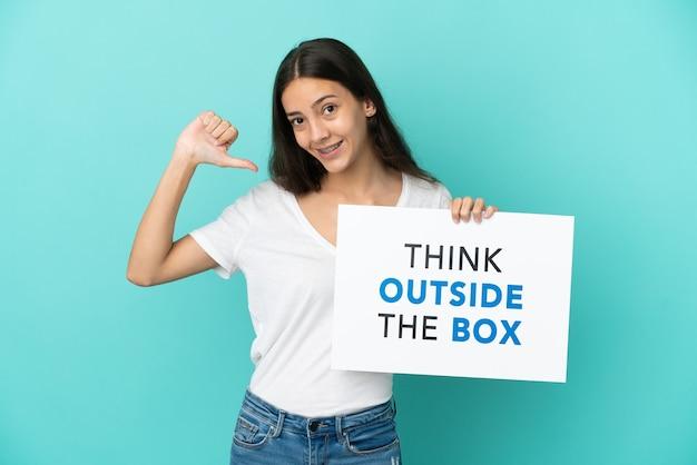 Jonge franse vrouw geïsoleerd met een bordje met tekst think outside the box met trots gebaar