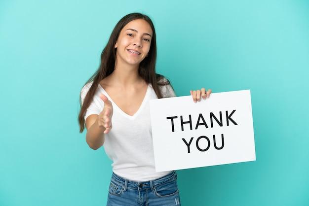 Jonge franse vrouw geïsoleerd op blauwe achtergrond met een bordje met de tekst bedankt om een deal te sluiten