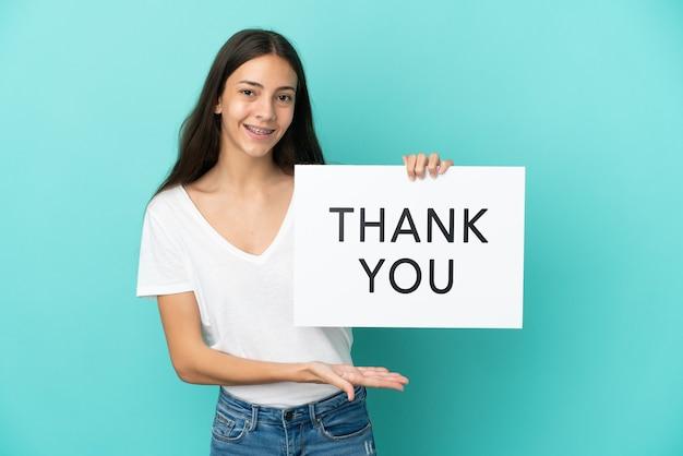 Jonge franse vrouw geïsoleerd op blauwe achtergrond met een bordje met de tekst dank u en erop wijzend