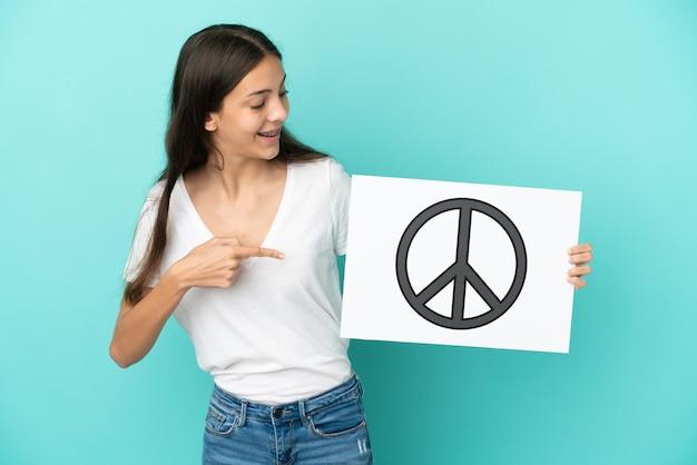 Jonge franse vrouw geïsoleerd op blauwe achtergrond met een bordje met vredessymbool en erop wijzend