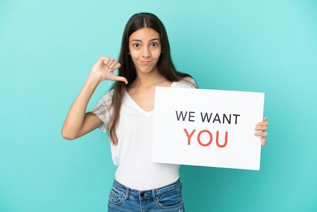 Jonge franse vrouw geïsoleerd op blauwe achtergrond met we want you board met trots gebaar