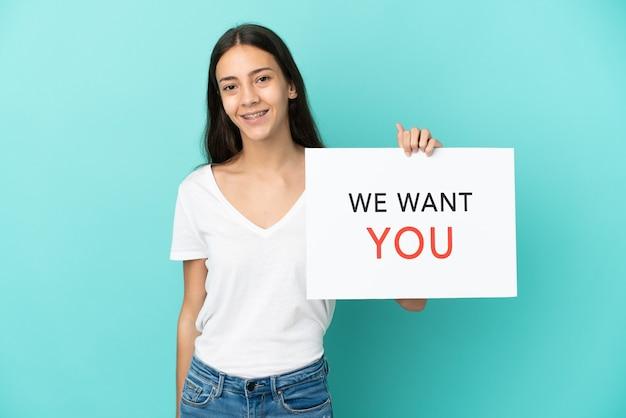 Jonge franse vrouw geïsoleerd op blauwe achtergrond met we want you bord met gelukkige uitdrukking