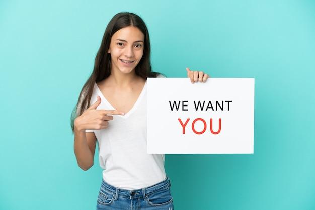 Jonge franse vrouw geïsoleerd op een blauwe achtergrond die we want you-bord vasthoudt en erop wijst