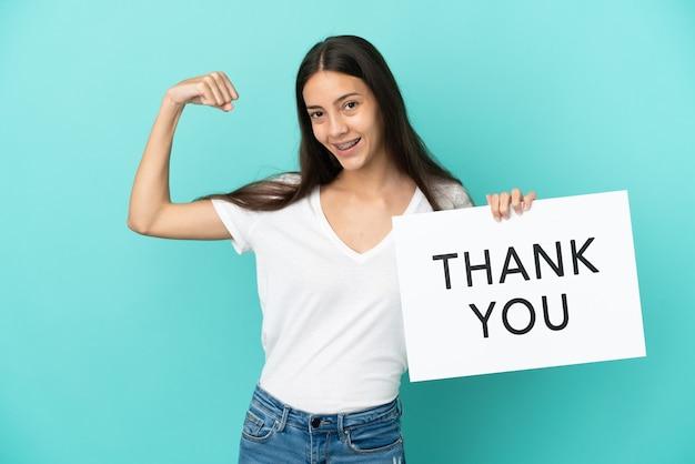 Jonge franse vrouw geïsoleerd op een blauwe achtergrond met een bordje met de tekst dank u en een sterk gebaar te maken