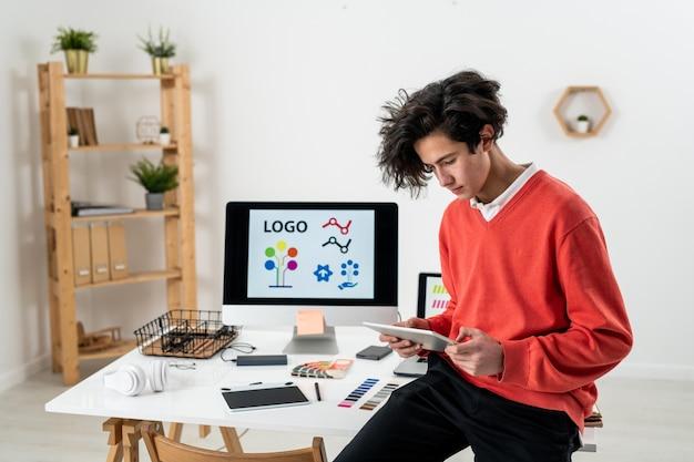 Jonge freelance ontwerper met behulp van touchpad zittend op een bureau met computermonitor en andere werkende benodigdheden