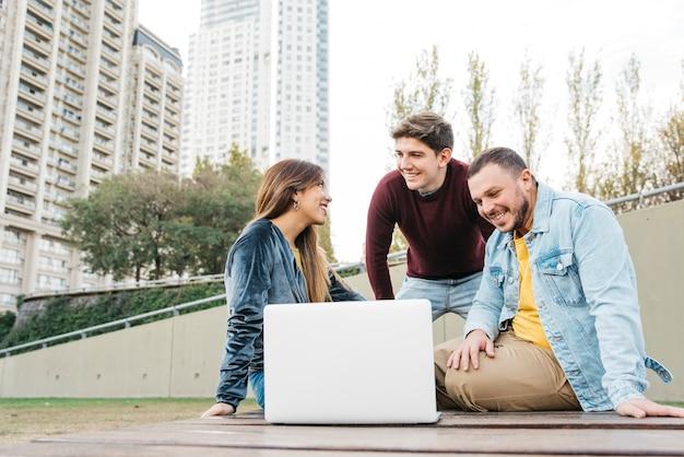 Jonge freelance studenten die buiten aan laptop werken