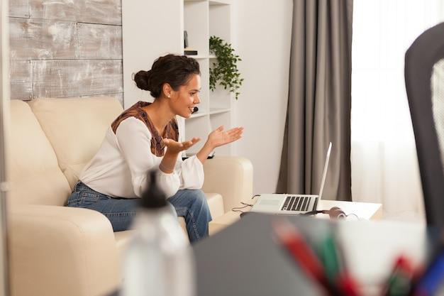 Jonge freelancer-vrouw die lacht tijdens een videogesprek op laptop die vanuit huis werkt.