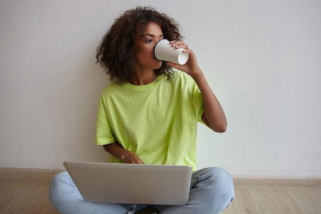Jonge freelancer vrouw met donkere huid en bruin krullend haar op afstand werken met laptop, zittend op de vloer en koffie drinken, vrijetijdskleding dragen