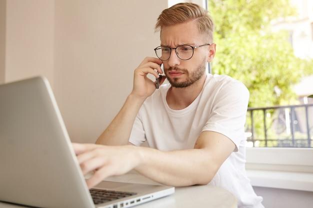 Jonge freelancer zit in café en werkt op afstand, draagt een bril en een wit t-shirt, kijkt gefronst en kijkt geconcentreerd op toegewezen taken