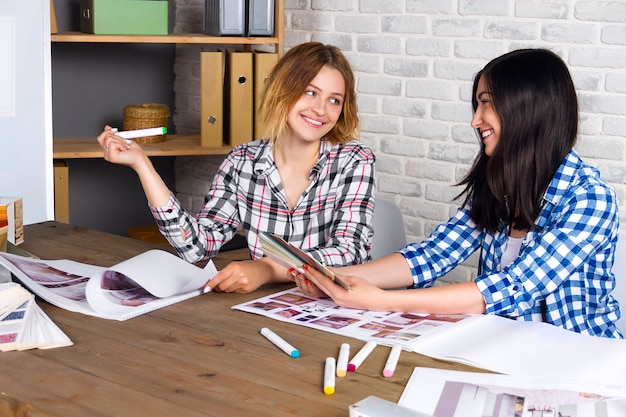Jonge freelancers interieurontwerpers werken nieuw appartementproject in ontwerpstudio uit. de vrouwelijke vergadering van het twee vrouwenmeisje met ontmoet bureau met speld op schetstekeningen en ontwerpen van nieuw project