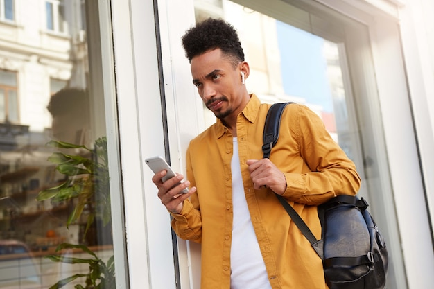 Jonge fronsende donkere man, aan de telefoon met zijn vriendin, kijkend van onder zijn voorhoofd met een verontwaardigde uitdrukking, zijn vriendin is weer te laat.