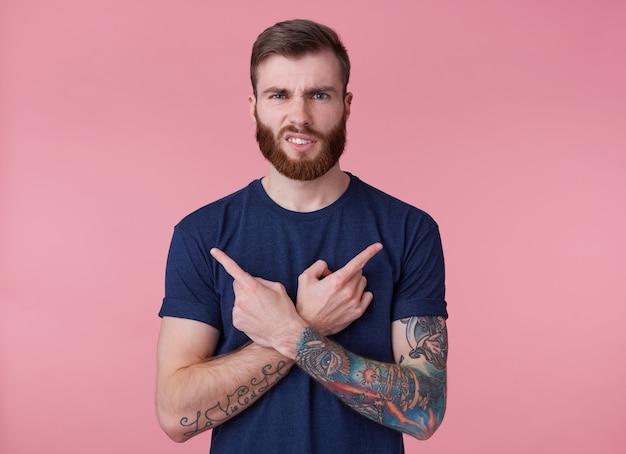 Jonge fronsende man met rode baard, bedrogen, vingers gekruist, vingers in verschillende richtingen wijzend, geïsoleerd op roze achtergrond.