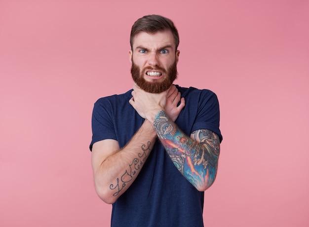 Jonge fronsende man met rode baard, kan geen uitweg vinden, ontevreden en boos, probeert zichzelf te wurgen, fronsend en grijnzend geïsoleerd over roze achtergrond.