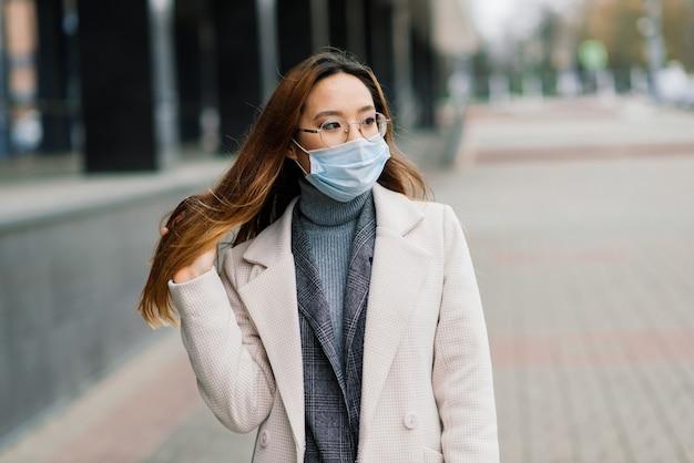 Jonge fsian-vrouw die gezichtsmasker draagt, staat in een binnenlandse straat.