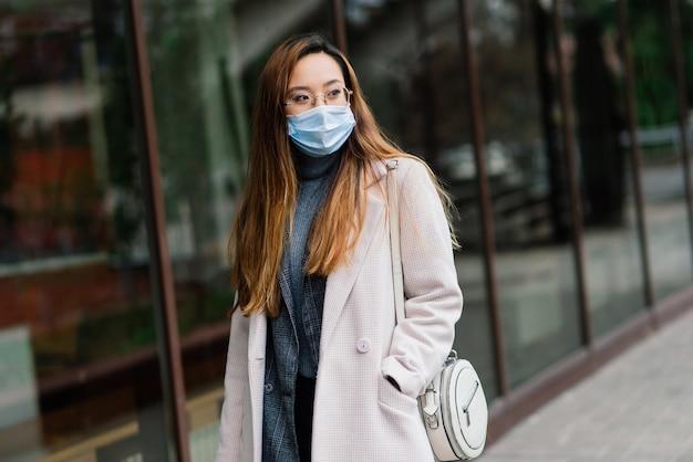 Jonge fsian vrouw met gezichtsmasker staat op een binnenlandse straat. concept nieuw normaal van pendelaars na covid-19-epidemie