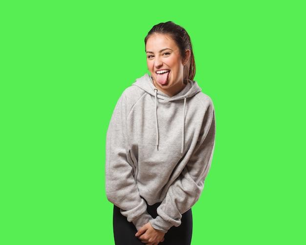 Jonge funnny fitnessvrouw en vriendelijke tonende tong