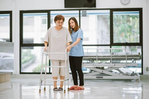 Jonge fysiotherapeut die senior patiënt helpt bij het gebruik van rollator tijdens revalidatie