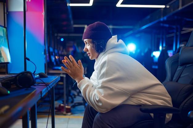Jonge gamer die in gaming-fauteuil rust, gameclub