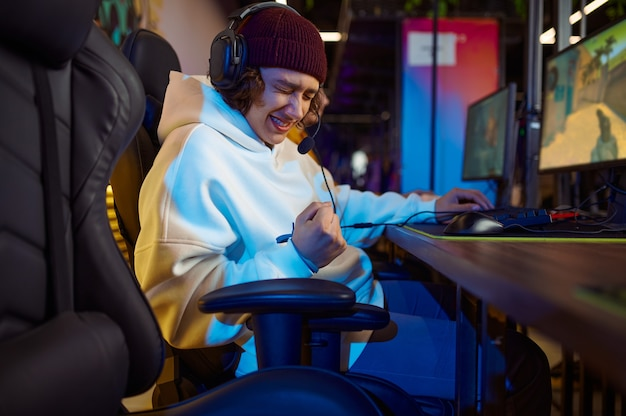 Jonge gamer in koptelefoon speelt in gameclub