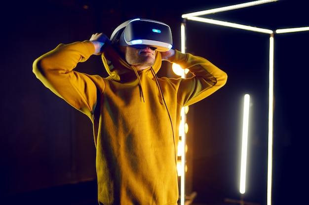 Jonge gamer speelt het spel met behulp van virtual reality-helm en gamepad in lichtgevende kubus