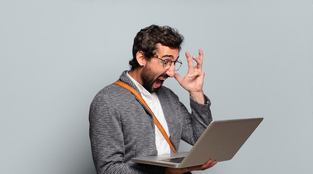 Jonge, gebaarde en gekke zakenman met laptop