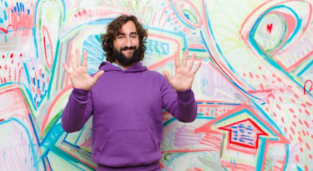 Jonge gebaarde gekke en mens die vriendelijk glimlachen kijken, nummer tien of tiende met vooruit hand tonen, die tegen graffitimuur aftellen