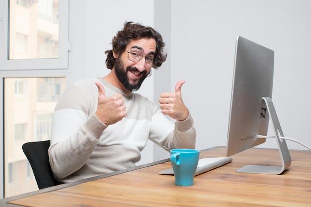 Jonge gebaarde gekke freelancer die met zijn computer werkt
