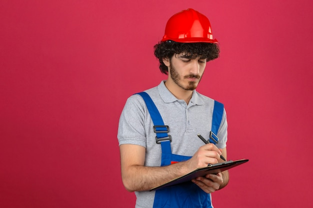 Jonge gebaarde knappe bouwer die eenvormige bouw dragen en het klembord van de veiligheidshelmholding en pen die iets met ernstig gezicht over geïsoleerde roze muur schrijven