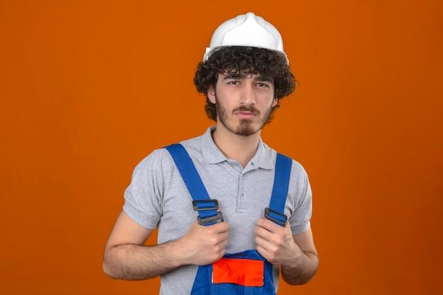 Jonge gebaarde knappe bouwer die eenvormige bouw dragen en veiligheidshelm die zich met afkeurende uitdrukking op gezichts negatieve persoon bevinden over geïsoleerde oranje muur