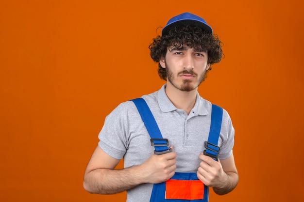 Jonge gebaarde knappe bouwer eenvormige bouw dragen en glb die zich met afkeurende uitdrukking op gezichts negatieve persoon bevinden over geïsoleerde oranje muur