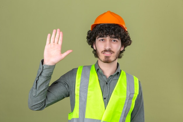 Jonge gebaarde knappe ingenieur die groetgebaar maken golvend met hand glimlachend over geïsoleerde groene muur