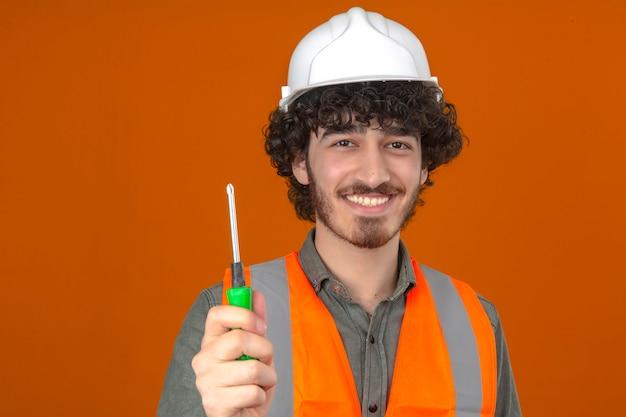 Jonge gebaarde knappe ingenieur die veiligheidshelm en vestschroevedraaier dragen die ter beschikking vrolijk over geïsoleerde oranje muur glimlachen