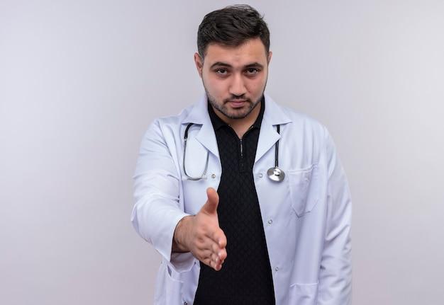 Jonge, gebaarde mannelijke arts die witte laag met stethoscoopgroet draagt met zelfverzekerde blik die hand aanbiedt
