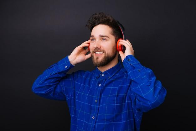 Jonge gebaarde mens die opzij het luisteren aan de muziek door een rode hoofdtelefoon op zwarte achtergrond kijkt.